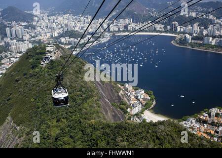 Monorail leaving Morro da Urca toward the Pao de Acucar - Botafogo Beach and Inlet Incidental - Stock Photo