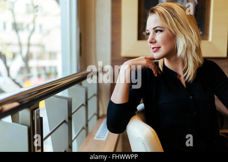 Blonde businesswoman looking out the window - Stock Photo