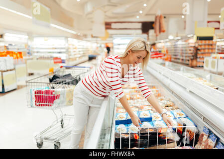 Beautiful woman shopping  and choosing food in supermarket - Stock Photo