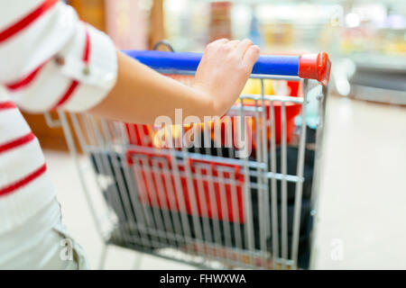 Woman shopping in supermarket and filling shopping cart - Stock Photo