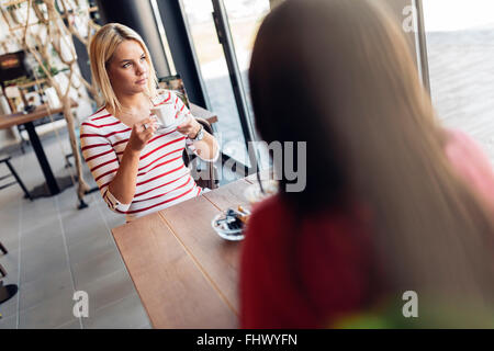 Beautiful women drinking coffee and gossiping in nice restaurant - Stock Photo