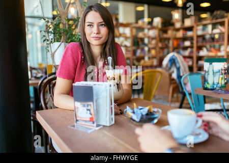 Beautiful woman talking to friend in restaurant while drinking coffee - Stock Photo