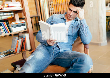 Handsome man studying by reading books and preparing for exam - Stock Photo