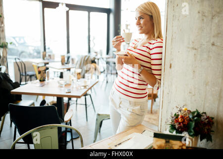 Portrait of a beautiful woman drinking coffee, tea in a cafe - Stock Photo