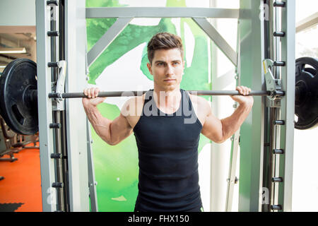 Handsome man training in gym to stay fit and strong - Stock Photo
