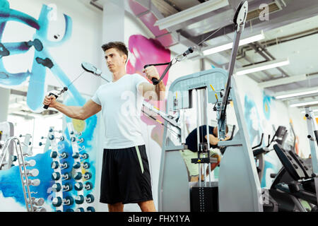 Handsome man training in clean modern gym on various machines - Stock Photo