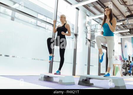 Beautiful women exercising aerobics in nice fitness club - Stock Photo