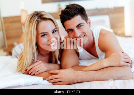 Happy husband loving wife while  lying in bed - Stock Photo