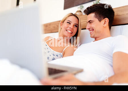 Beautiful couple using laptop in bed while being truly happy - Stock Photo