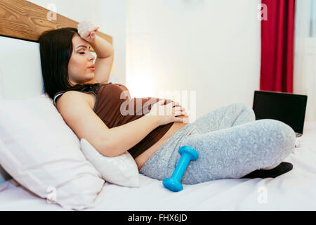 Tired beautiful pregnant woman resting after exercising at home - Stock Photo