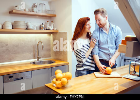 Happy couple making organic juice in kitchen and smiling - Stock Photo