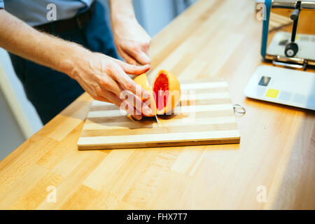 Man slicing orange in kitchen with knife - Stock Photo
