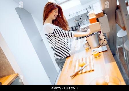 Beautiful woman squeezing oranges in order to prepare hommade juice - Stock Photo