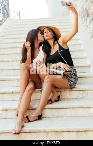 Good friends taking a selfie of themselves while sitting on stairs - Stock Photo