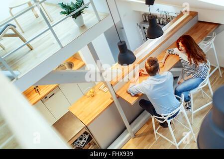 Beautiful couple in pristine home talking - Stock Photo