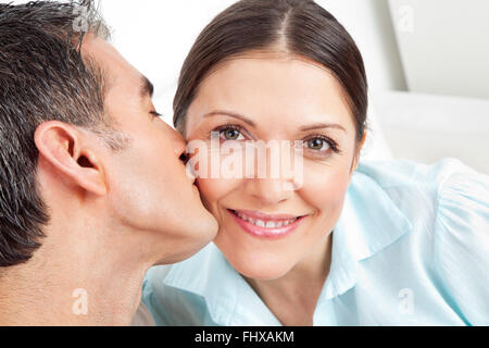 Elderly man kissing his smiling woman on the cheek - Stock Photo