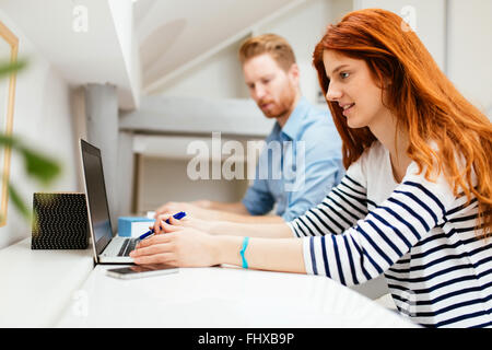 Husband and wife working from home on laptop - Stock Photo