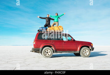 Bolivia, Salar de Uyuni, Couple kneeling on a 4x4 car - Stock Photo