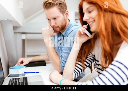 Colleagues working studying in white modern office - Stock Photo