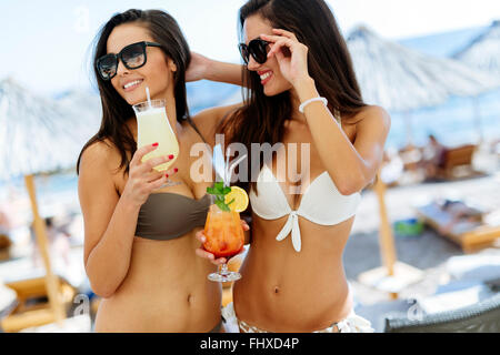 Beautiful girls drinking cocktails on beach and having a good time - Stock Photo
