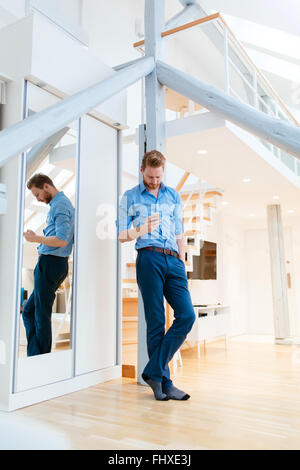 Man using phone in beautiful modern apartment wearing shirt - Stock Photo