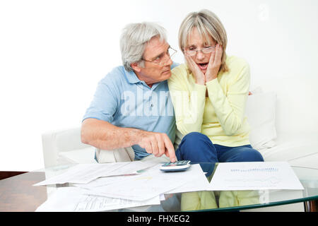 Worried senior couple sitting with bills and calculator at home - Stock Photo