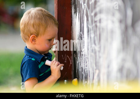 Creative cute toddler drawing with chalk outdoors on a drawing board - Stock Photo