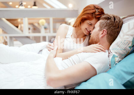 Beautiful couple in love awake  in bed and smiling - Stock Photo