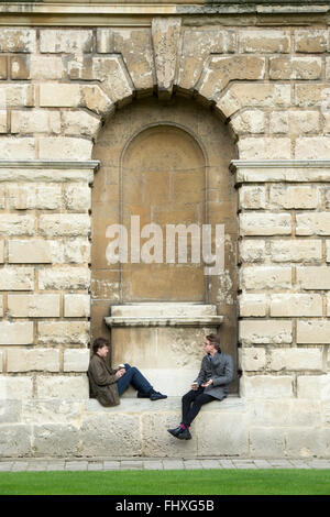 Two students sitting around Radcliffe camera. Oxford, Oxfordshire, UK - Stock Photo