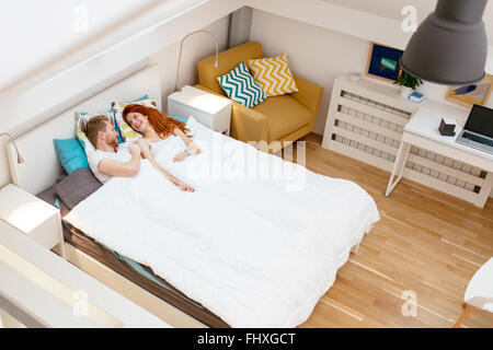 Romantic couple resting in bed and bonding during weekend - Stock Photo