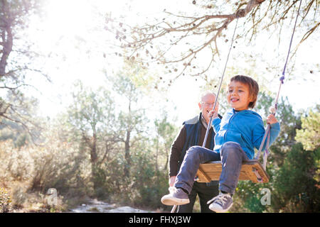 Spain, Siurana, little boy having fun on a swing while his grandfather watching him - Stock Photo