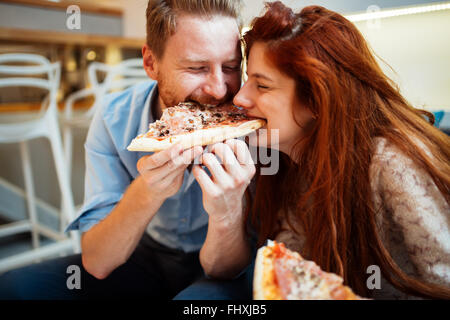 Couple sharing pizza and eating together happily - Stock Photo