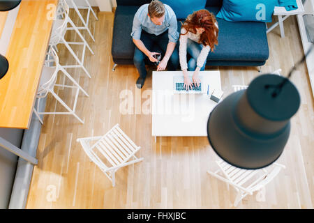 Couple browsing web together in living room viewed from above - Stock Photo