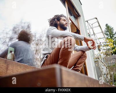 Young man relaxing on terrace - Stock Photo