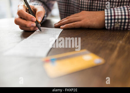 Close-up of man signing bill on table - Stock Photo