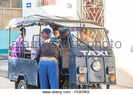 Cuban man fixing a homemade taxi. The vehicle is made from spare parts such as wheels and pistons, parts that can - Stock Photo
