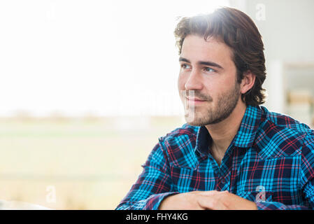 Portrait of relaxed man with brown hair wearing checked shirt - Stock Photo