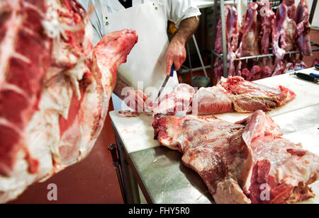 Unidentifiable butcher in white apron cutting pieces of meat with knife - Stock Photo