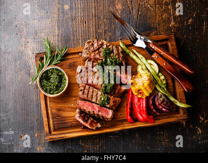 Sliced Striploin steak with chimichurri sauce and Grilled vegetables on cutting board on dark background - Stock Photo