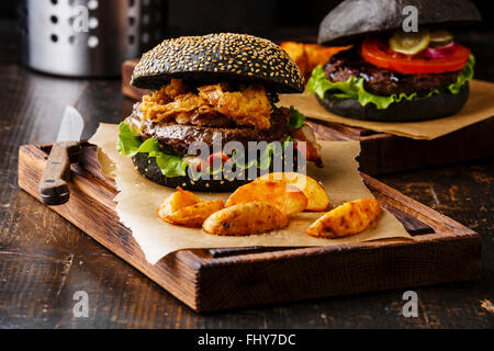 Black burger with sesame seed bun meat bacon onion fries rings and potato wedges on dark wooden background - Stock Photo