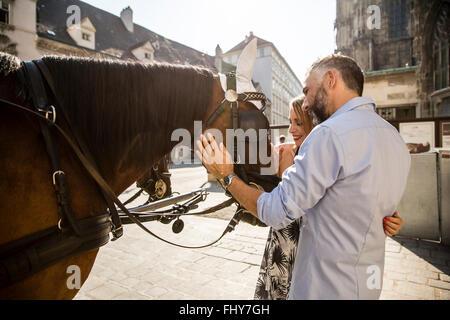 Austria, Vienna, couple stroking horse at Stephansplatz - Stock Photo