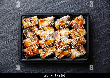 Eel Sushi rolls in plastic box packaging tray on black stone slate background - Stock Photo