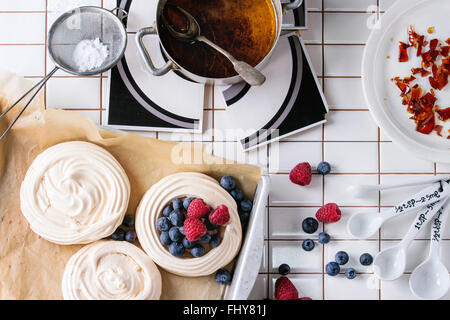 Fresh baking meringue for Pavlova dessert with berries sugar powder and caramel over white tiled kitchen table. - Stock Photo