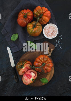 Fresh ripe hairloom tomatoes and basil leaves on rustic wooden board over black stone background. top view - Stock Photo