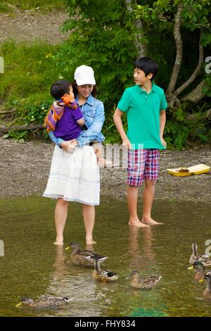 Asian mother baby and boy standing in river watching ducks. - Stock Photo