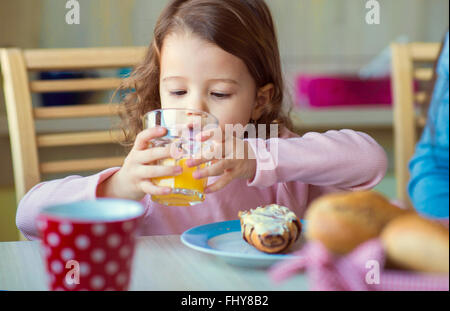 Portrait of little girl drinking glass of orange juice at breakfast table - Stock Photo