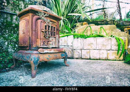 old fireplace in the garden whit flowers - Stock Photo
