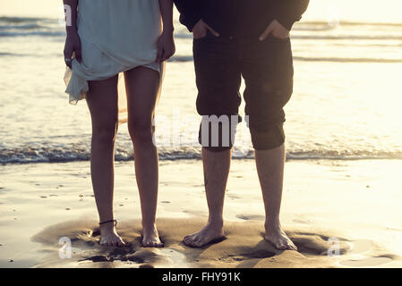 Spain, Cadiz, legs of young couple standing barefoot atseafront - Stock Photo
