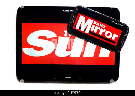 The logos of The Sun and the Daily Mirror newspapers displayed on the screens of a tablet and a smartphone. - Stock Photo