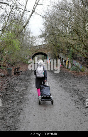 Rear view of older woman walking on parkland walk path with wheeled trolley cart in Crouch End, London UK  KATHY - Stock Photo